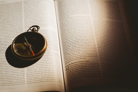 quaker: Compass on open bible in the shadow