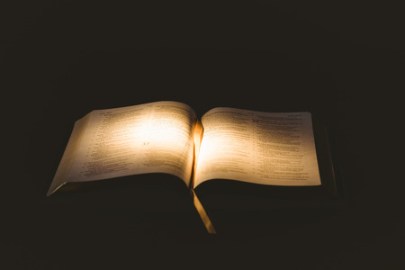 brethren: Light shining on open bible on black background