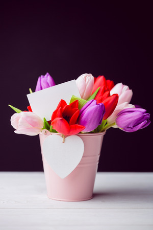 Bunch of tulips and white card on black background photo