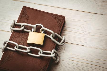 biblia: Abra la biblia en cadena con candado en mesa de madera Foto de archivo