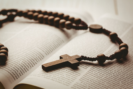 jehovah: Open bible and wooden rosary beads on wooden table Stock Photo