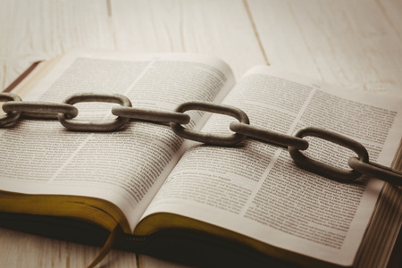 jehovah: Open bible and heavy chain on wooden table