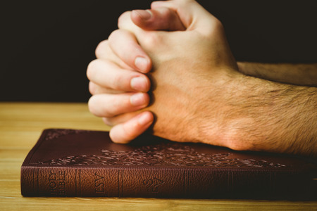 mormon: Man praying over his bible on wooden table