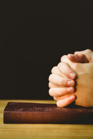 jehovah: Man praying with his bible on wooden table Stock Photo