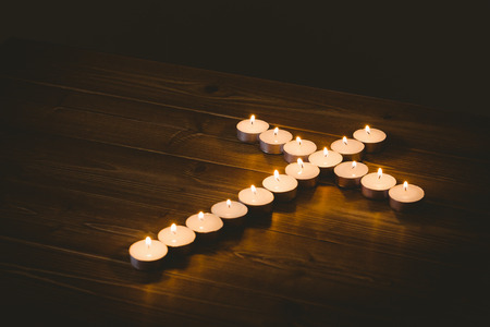 quaker: Candles in shape of cross on wooden table