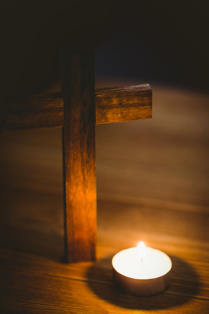 brethren: Candle and wooden cross on wooden table