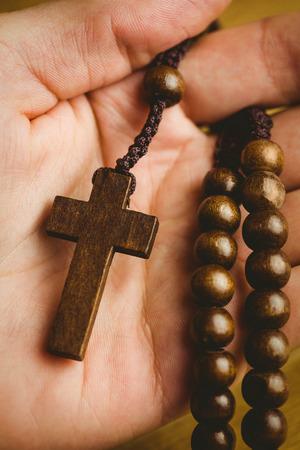brethren: Hand holding wooden rosary beads overhead shot