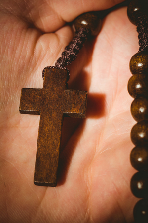 jehovah: Hand holding wooden rosary beads in close up