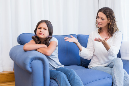 reprimanding: Upset mother looking at her daughter in the living room Stock Photo