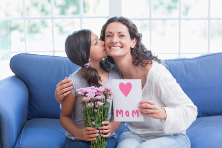 cheek to cheek: Cute girl offering flowers and card to her mother in the living room