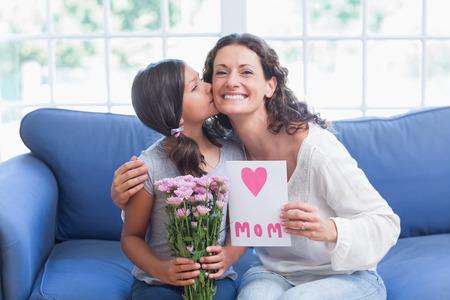madre: Linda chica ofreciendo flores y la tarjeta a su madre en la sala de estar