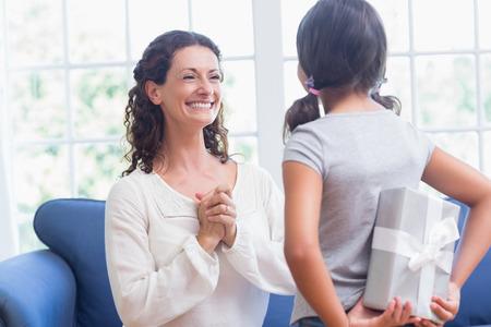 Linda chica ofreciendo regalo a su madre en la sala de estar Foto de archivo - 38516007