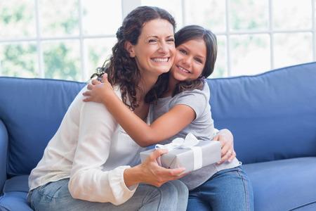 Glückliche Mutter und Tochter umarmt und lächelnd in die Kamera im Wohnzimmer Standard-Bild - 38516010