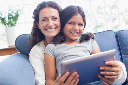 Happy mother and daughter sitting on the couch and using tablet in the living room photo