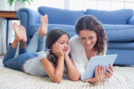 curly hair child: Happy mother and daughter lying on the floor and using tablet in the living room Stock Photo