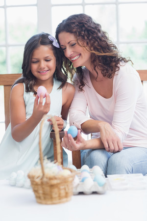 Happy mother and daughter holding easter eggs in the living room photo