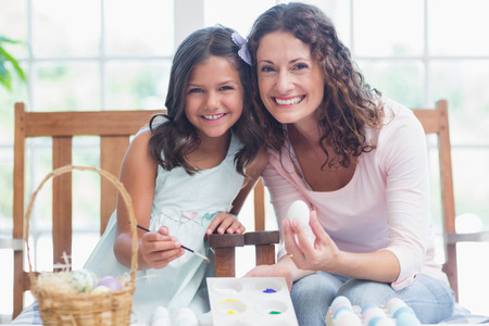 curly hair child: Happy mother and daughter painting easter eggs in the living room