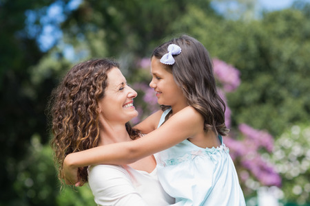 family with one child: Happy mother and daughter smiling at each other in the garden