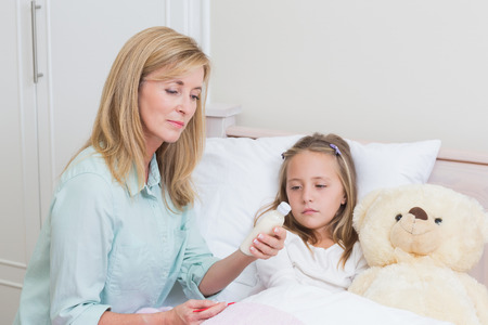 cough medicine: Mother giving her daughter cough medicine in bed Stock Photo
