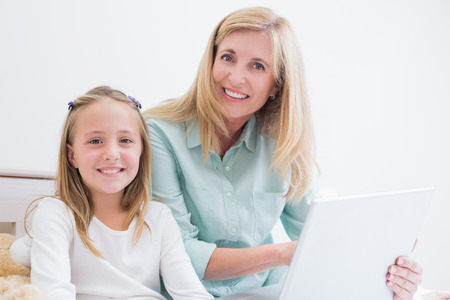 Happy mother and daughter using laptop in bed photo