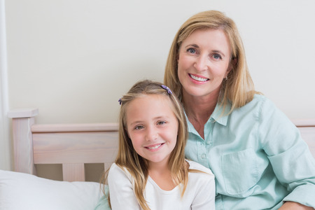 one family: Happy mother and daughter smiling at camera in the bedroom Stock Photo