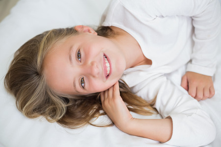 domicile: Happy girl smiling at camera in bed Stock Photo