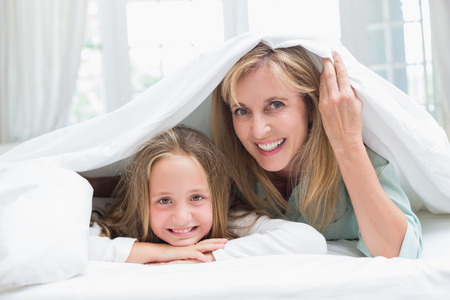 duvet: Mother and daughter looking at camera under the duvet at home in the bedroom