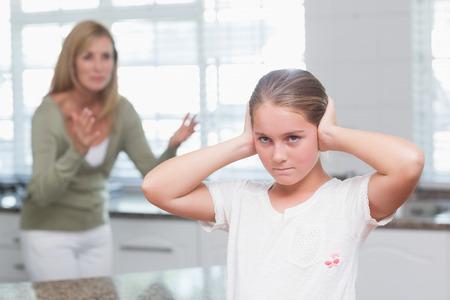 mujeres peleando: Niña trastornada tapándose los oídos mientras su madre gritando en casa en la cocina
