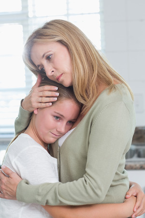 Sad little girl hugging her mother at home in the kitchen
