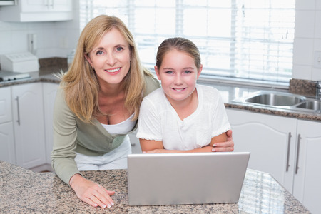 Smiling mother and daughter using laptop together at home in the kitchen photo