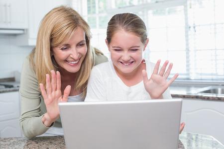 mujeres y niños: Madre e hija hablando con alguien con el portátil en casa en la cocina
