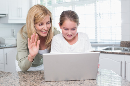 Mother and daughter talking with someone with the laptop at home in the kitchen photo
