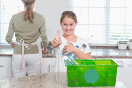 recycling bottles: Little girl holding recycling bottles with thumbs up at home in the kitchen