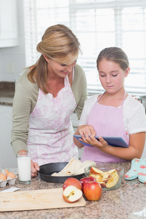Happy mother and daughter preparing cake together with tablet at home in the kitchen photo
