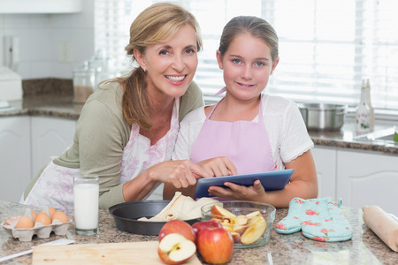 Happy mother and daughter preparing cake together at home in the kitchen photo