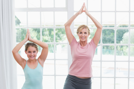 tree position: Mother and daughter doing yoga at home in living room