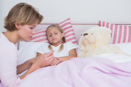 family with one child: Mother taking the temperature of sick daughter at home in the bedroom Stock Photo