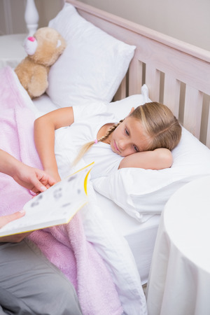 bedtime story: Mother reading daughter a bedtime story at home in the bedroom