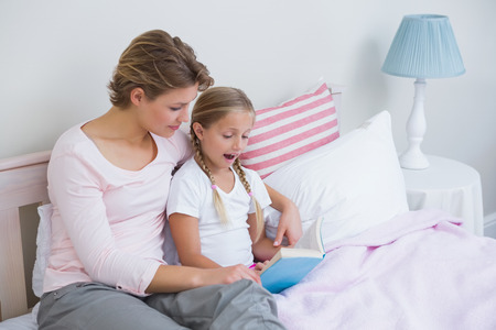 Mother with her daughter at bedtime at home in the bedroom