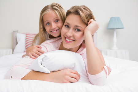Mother and daughter smiling at camera at home in the bedroom Stock Photo