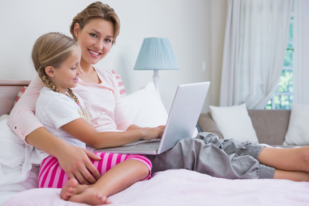 Mother and daughter using laptop in bed at home in the bedroom photo