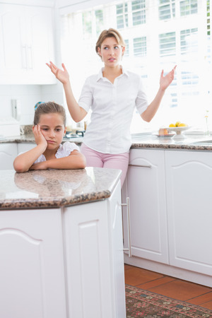 Mother and daughter after an argument at home in kitchen photo