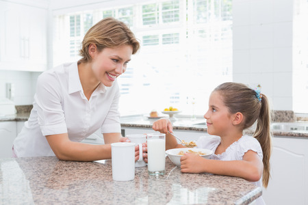 mother and children: Madre e hija que desayunan en casa en la cocina Foto de archivo