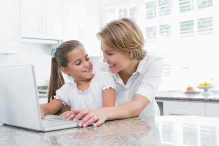 Mother and daughter using laptop at home in kitchen photo