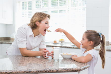 cereals: Mother and daughter having breakfast at home in kitchen