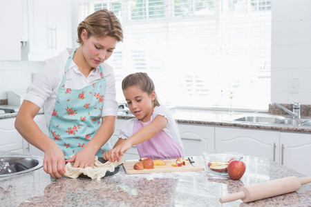 Mother and daughter baking together at home in kitchen photo
