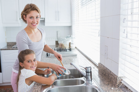 household tasks: Mother and daughter washing up at home in kitchen Stock Photo