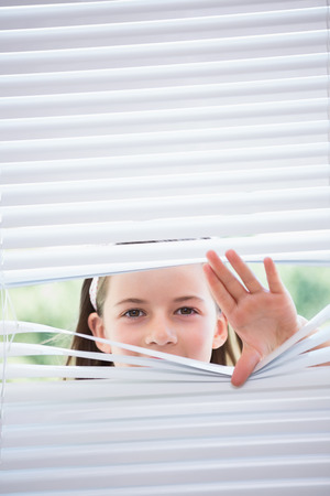nosey: Little girl peeking through blinds from outside Stock Photo