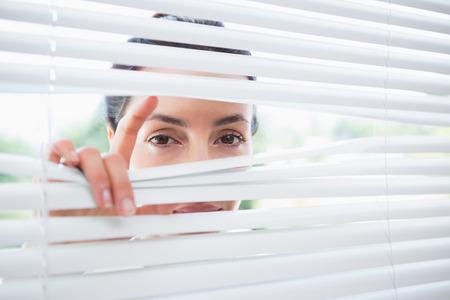 peeking: Woman peeking through blinds from outside