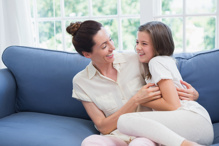 beautiful mother: Mother and daughter laughing on couch at home in the living room